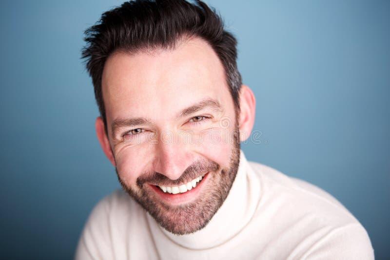 Fermez-vous vers le haut de l'homme heureux avec la barbe posant sur le fond bleu image stock