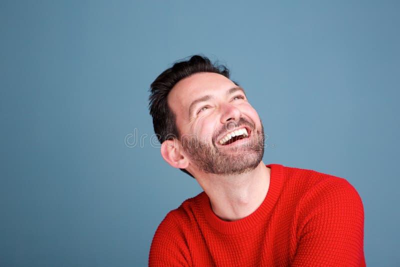 Fermez-vous vers le haut de l'homme heureux riant et recherchant sur le fond bleu photos libres de droits