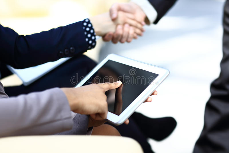 Fermez-vous vers le haut de l'homme multitâche de mains à l'aide du comprimé photos stock