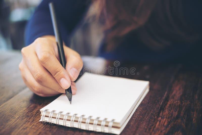 Fermez-vous vers le haut de l'image de l'écriture de main du ` s de femme sur le carnet avec la table en bois images stock