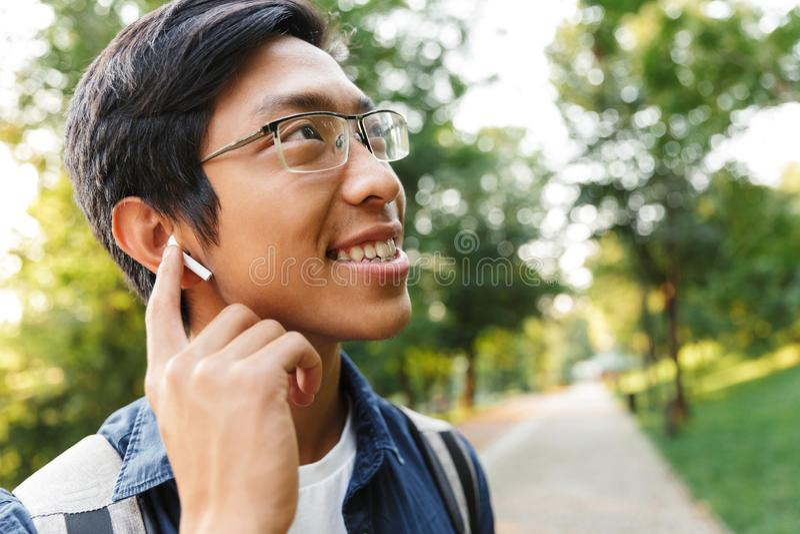 Fermez-vous vers le haut de l'image de l'étudiant masculin asiatique heureux dans des lunettes photo libre de droits