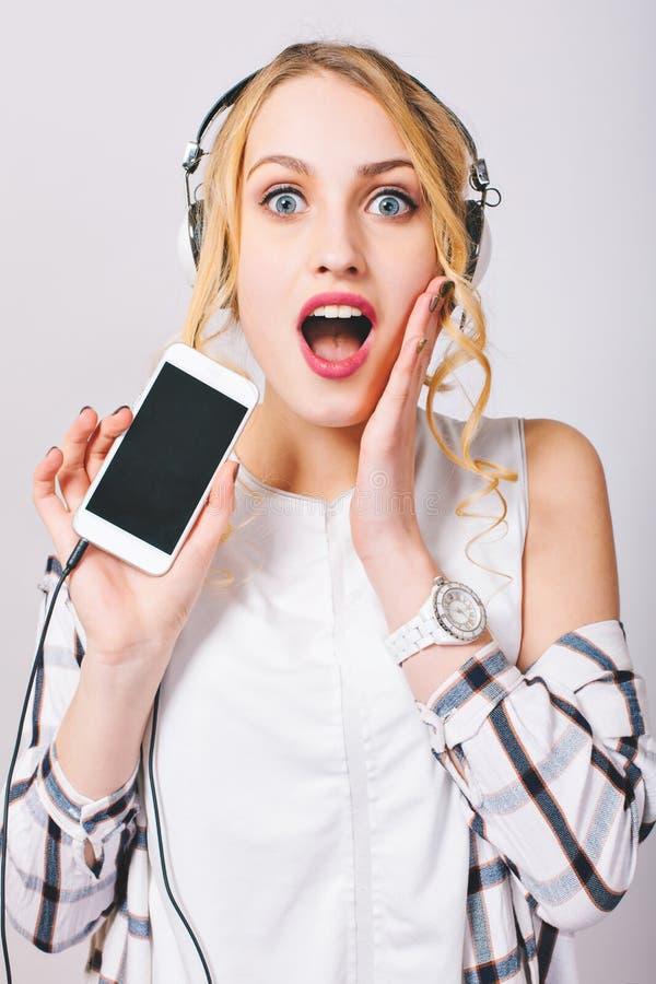 Fermez-vous vers le haut de l'image d'intérieur de la jeune femme mignonne gaie écoutant la musique par des écouteurs, téléphone  image stock