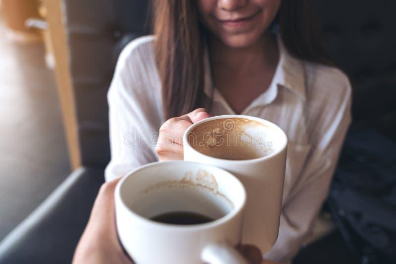 Fermez-vous vers le haut de l'image d'un homme et des tasses de café blanc tintantes de femme images libres de droits