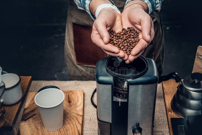 Fermez-vous vers le haut de l'image d'un homme mettant des grains de café dans un machi de café photo stock
