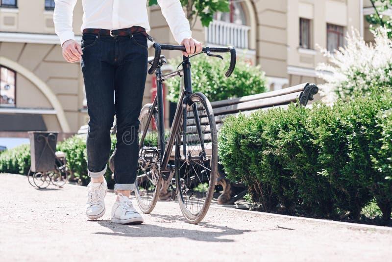 Fermez-vous vers le haut de l'image extérieure du jeune homme de hippie dans les jeans et des chaussures au vélo moderne élégant  images stock