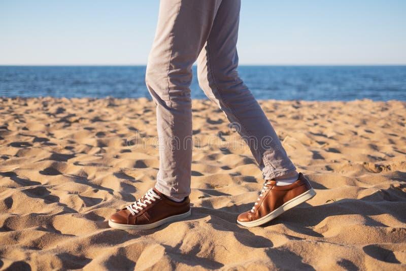 Fermez-vous vers le haut de l'image plage sablonneuse de marche de l'homme de la seule avec l'océan bleu et le sable blanc photographie stock libre de droits
