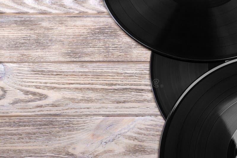 Fermez-vous vers le haut de l'image de vieux disques vinyle au-dessus de fond en bois avec l'espace de copie photographie stock libre de droits