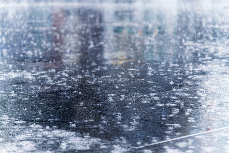 fermez-vous vers le haut de la baisse de l'eau de pluie tombant dans le plancher de rue de ville avec W photo stock