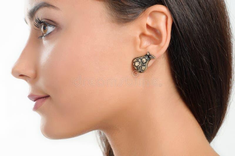 Fermez-vous vers le haut de la beauté de portrait avec la boucle d'oreille élégante et le long hai brun images stock