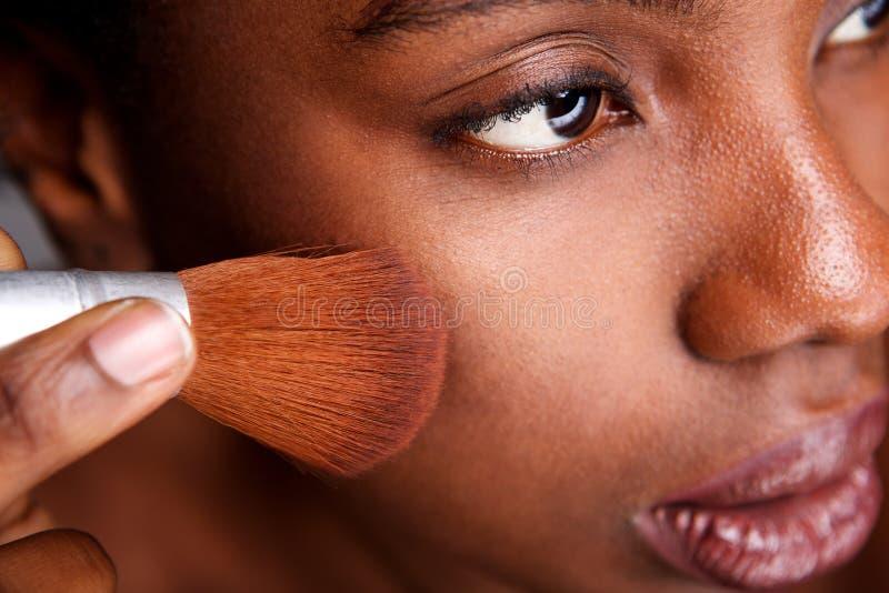Fermez-vous vers le haut de la belle femme appliquant le maquillage avec la brosse pour la finition mate lisse photos libres de droits
