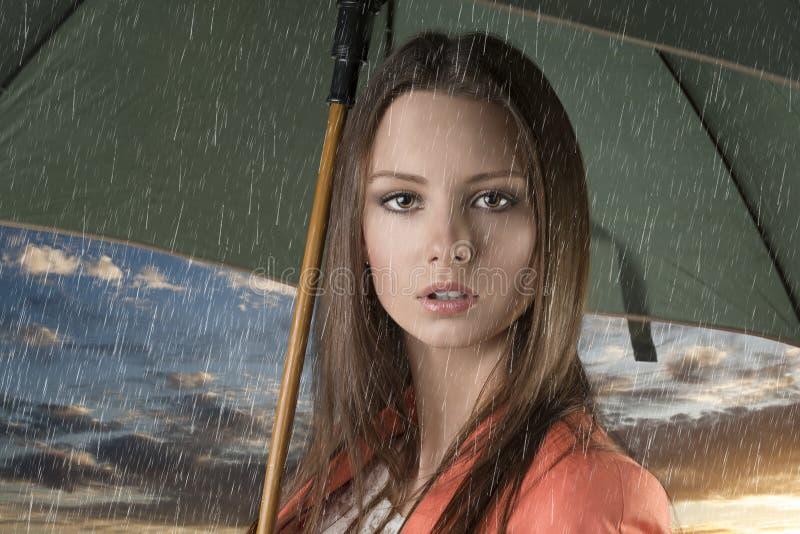 Fermez-vous vers le haut de la belle femme avec le parapluie sous la pluie photo stock