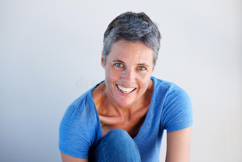 Fermez-vous vers le haut de la belle femme mûre souriant sur le fond blanc photographie stock