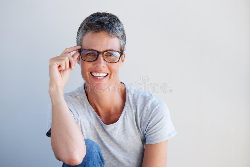 Fermez-vous vers le haut de la belle femme plus âgée souriant avec des verres contre le mur blanc photo stock