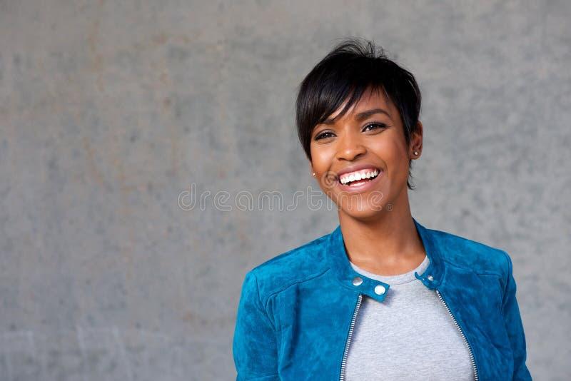 Fermez-vous vers le haut de la belle jeune femme de couleur avec le sourire de veste bleue image libre de droits