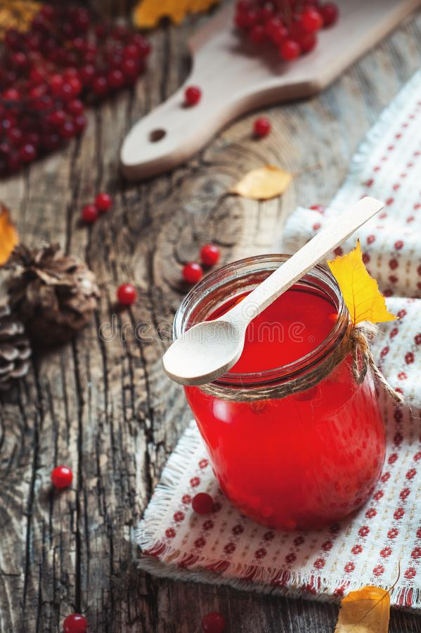 Fermez-vous vers le haut de la boisson rouge chaude en verre avec la baie de canneberge ou de viburnum sur la table en bois avec  images stock