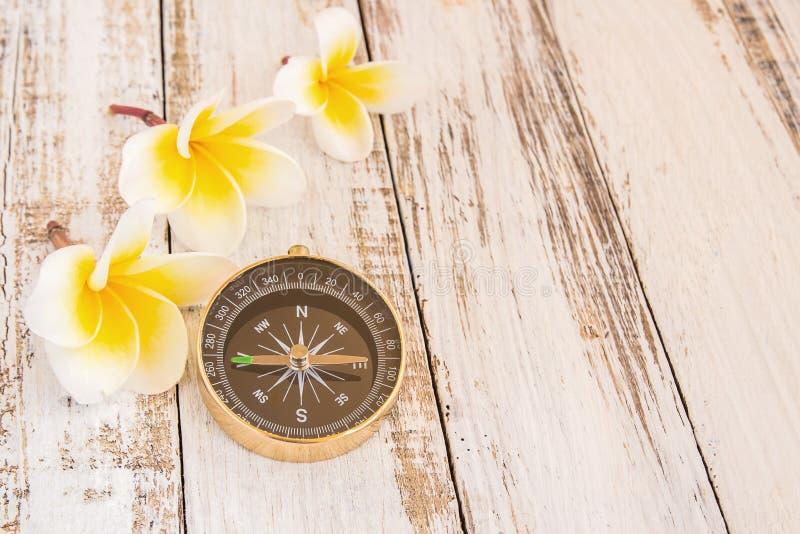 Fermez-vous vers le haut de la boussole et de la fleur tropicale de Plumeria sur la table en bois photos stock