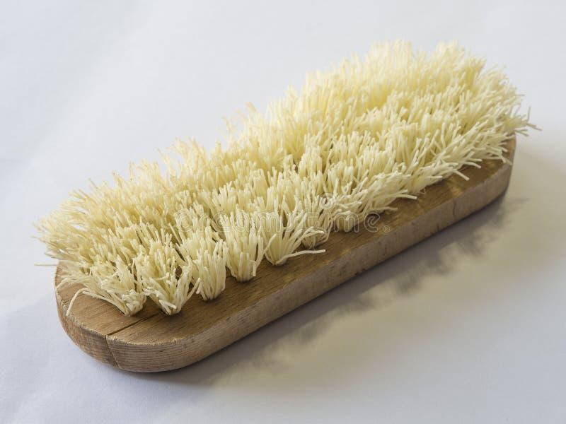 Fermez-vous vers le haut de la brosse de frottement en bois sur le fond blanc images stock