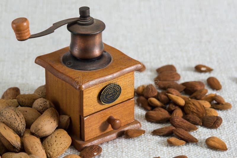 Fermez-vous vers le haut de la broyeur de café et avez épluché des amandes sur la texture beige de tissu photographie stock