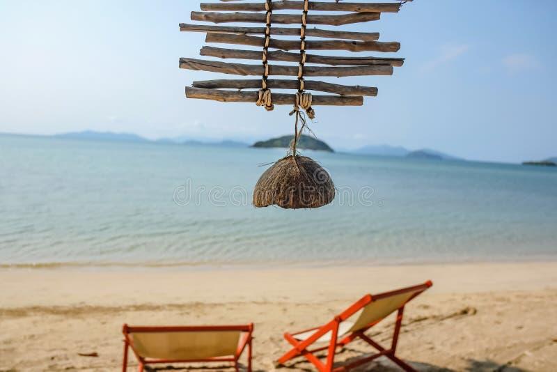 Fermez-vous vers le haut de la coquille de noix de coco avec l'océan idyllique et du beau ciel dans les vacances image libre de droits