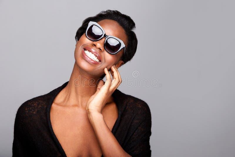 Fermez-vous vers le haut de la femme de couleur élégante souriant avec des lunettes de soleil photos libres de droits