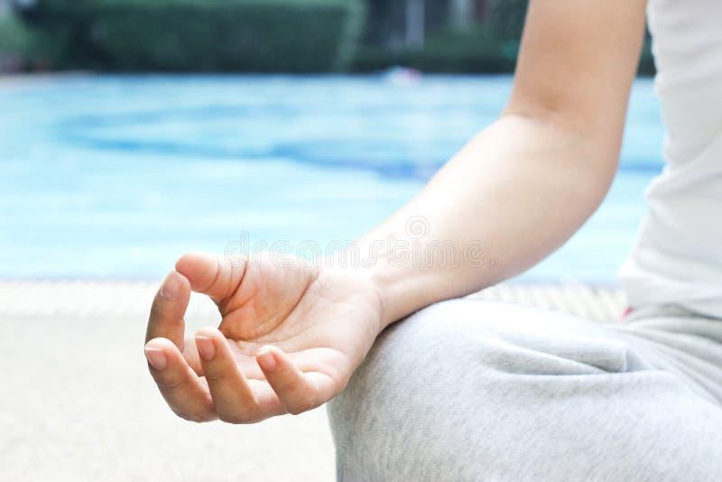 Fermez-vous vers le haut de la femme de main méditant en position de yoga de lotus à la station thermale de piscine photo stock