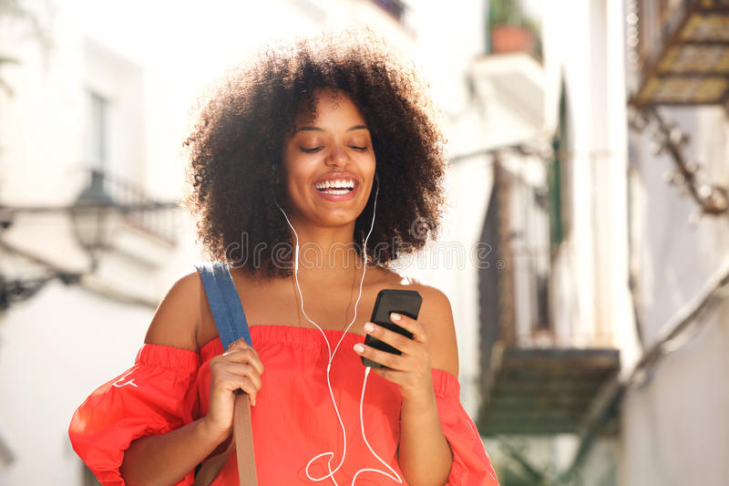 Fermez-vous vers le haut de la femme heureuse dehors sur la rue avec les écouteurs et le téléphone intelligent photo stock