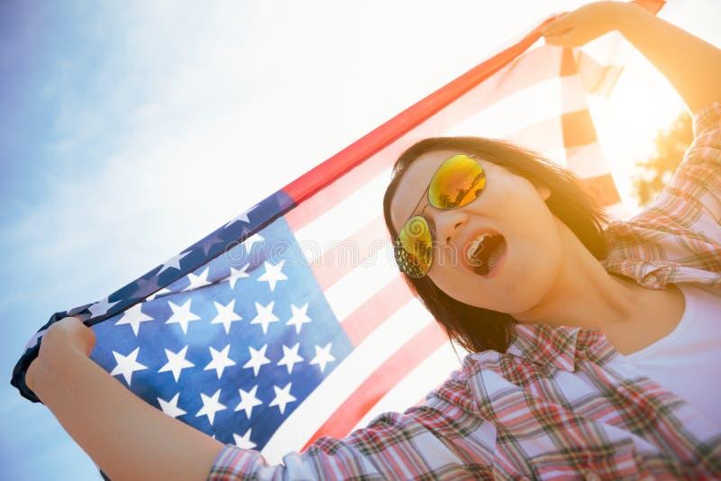 Fermez-vous vers le haut de la femme heureuse tenant le drapeau des Etats-Unis d'Amérique image libre de droits