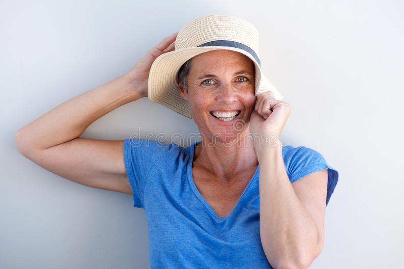 Fermez-vous vers le haut de la femme mûre heureuse souriant avec le chapeau sur le fond blanc photos stock