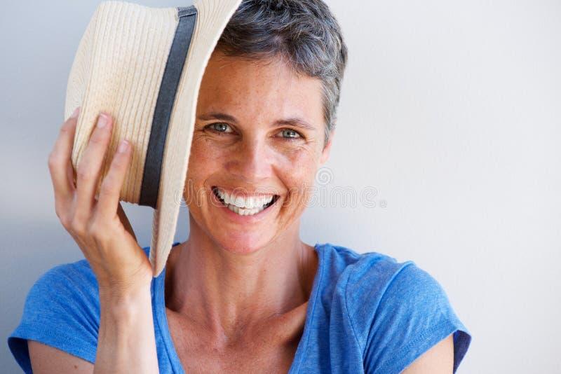 Fermez-vous vers le haut de la femme mûre de sourire avec le chapeau contre le mur blanc images stock