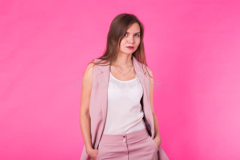 Fermez-vous vers le haut de la femme moderne d'affaires avec le fond de rose de l'espace, femme tenant la pose sûre Affaires occa image stock