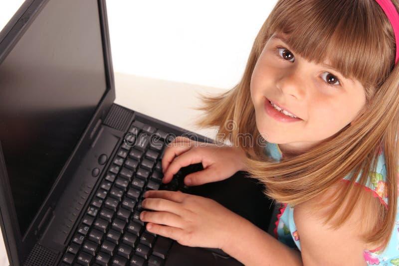 Fermez-vous vers le haut de la fille sur l'ordinateur portatif d'ordinateur photographie stock libre de droits