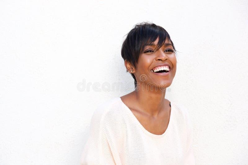 Fermez-vous vers le haut de la jeune dame noire à la mode riant sur le fond blanc photographie stock libre de droits
