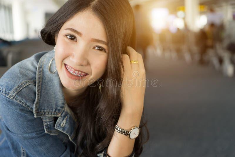 Fermez-vous vers le haut de la jeune femme asiatique de portrait dans le terminal d'aéroport photo stock