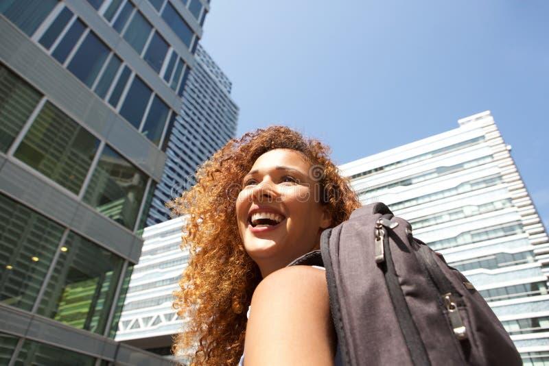 Fermez-vous vers le haut de la jeune femme heureuse avec le sac marchant dans la ville photo libre de droits