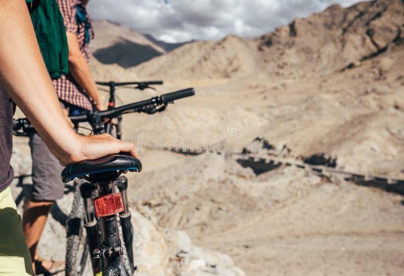 Fermez-vous vers le haut de la main d'homme d'image sur la selle de bicyclette Deux cyclistes de maountain photo libre de droits