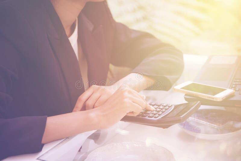 Fermez-vous vers le haut de la main de femme utilisant la calculatrice et le PC de carnet avec calculent au sujet du coût commenc photo libre de droits