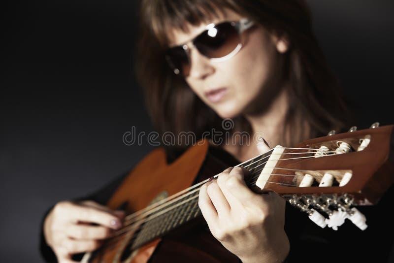 Fermez-vous vers le haut de la main de la fille jouant la guitare. image libre de droits