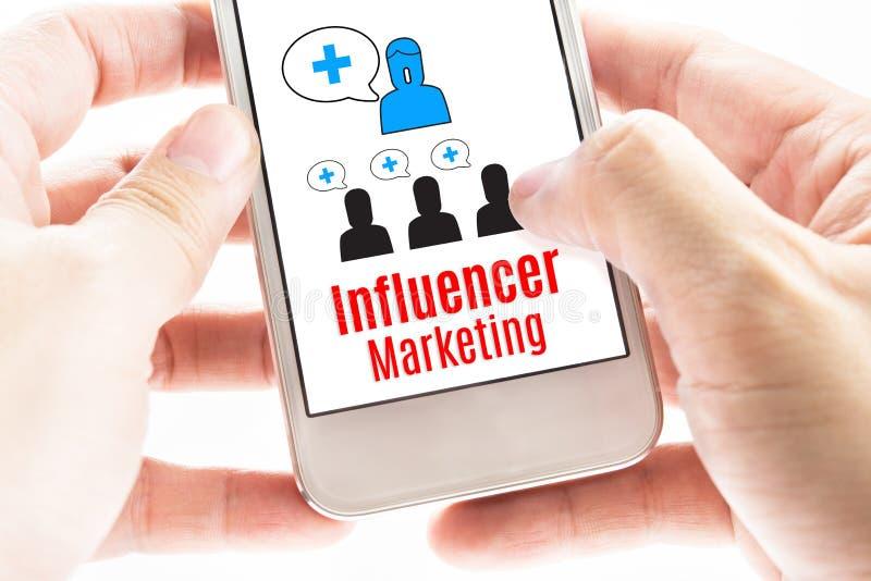 Fermez-vous vers le haut de la main deux tenant le téléphone intelligent avec le marketing d'Influencer image stock