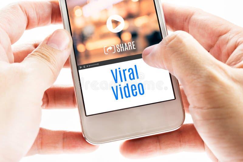Fermez-vous vers le haut de la main deux tenant le téléphone intelligent avec le mot visuel viral et photographie stock libre de droits
