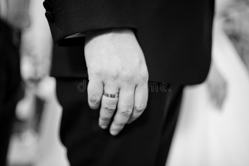 Fermez-vous vers le haut de la main du marié avec l'anneau de mariage à la cérémonie d'église blA image libre de droits