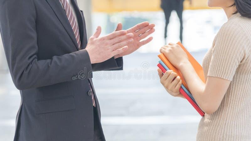 Fermez-vous vers le haut de la main du professeur et du rassemblement de l'adolescence d'étudiants et parlez à l'outd images libres de droits