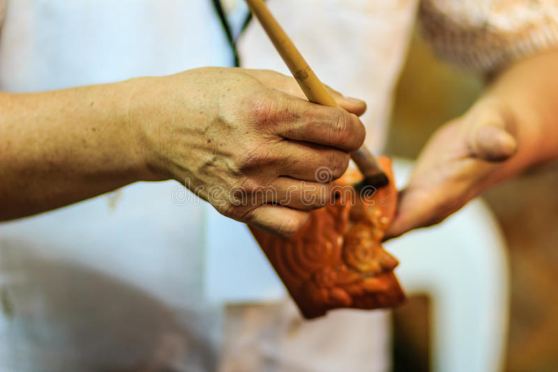 Fermez-vous vers le haut de la main du sculpteur thaïlandais pendant la peinture du chef d'oeuvre o image stock