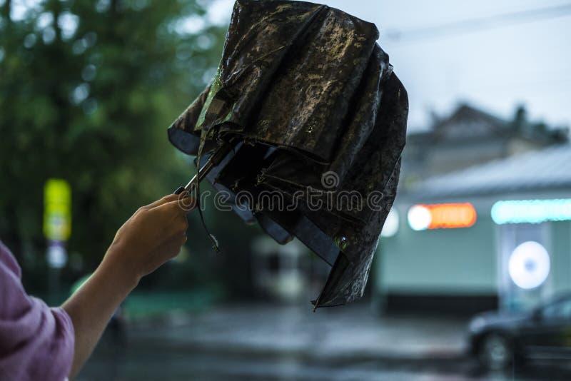 Fermez-vous vers le haut de la main de femme ouvrant le parapluie pendant la pluie dans la ville images libres de droits