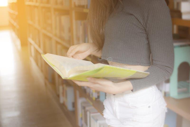 Fermez-vous vers le haut de la main fille sexy d'Asain de la jeune tenant un livre et un standi image stock