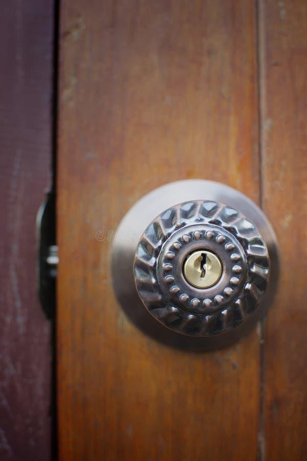 Fermez-vous vers le haut de la maison ouverte de bouton de porte en métal sur une vieille porte en bois photos stock