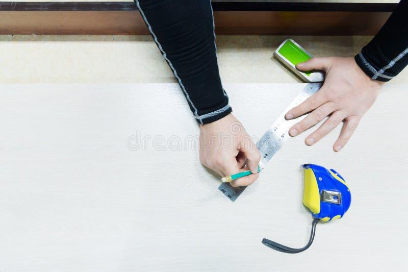 Fermez-vous vers le haut de la menuiserie, équipez la main utilisant le ruban métrique de mesurer la planche en bois et la marque photo stock