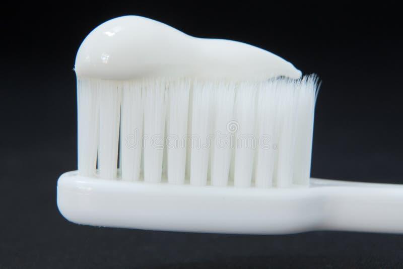 Fermez-vous vers le haut de la pâte dentifrice sur le doux blanc de brosse à dents et lissez l'isolat images stock