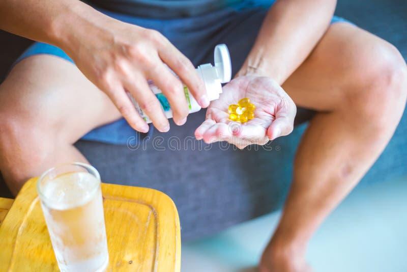 Fermez-vous vers le haut de la photo d'une pilule jaune ronde à disposition L'homme prend des médecines avec le verre de l'eau No photos stock