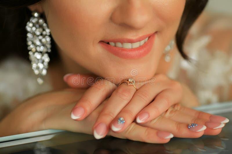 Fermez-vous vers le haut de la photo de la bouche et de la main de la jeune jeune mariée avec l'anneau de mariage images libres de droits