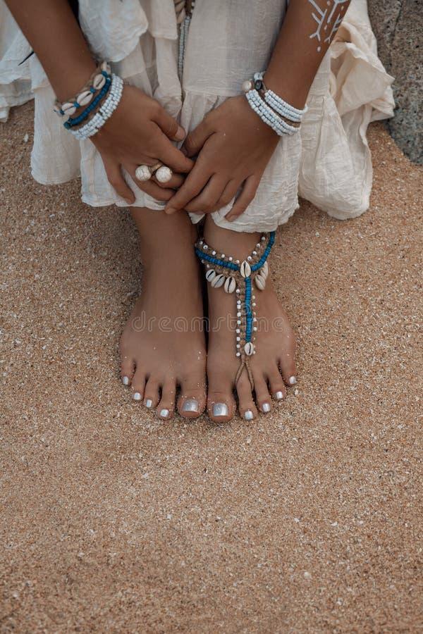 Fermez-vous vers le haut de la photo des jambes avec les chaînes de cheville élégantes image libre de droits